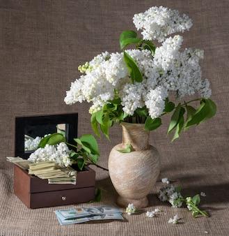 꽃병에 라일락 꽃이 피고 가슴에 달러가 있는 정물