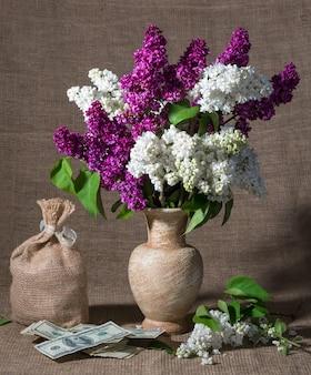 꽃병과 달러에 라일락 꽃 가지가 있는 정물