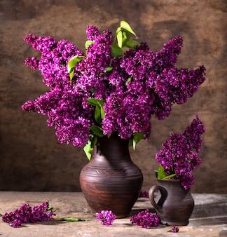 꽃병에 라일락 꽃 가지가 있는 정물