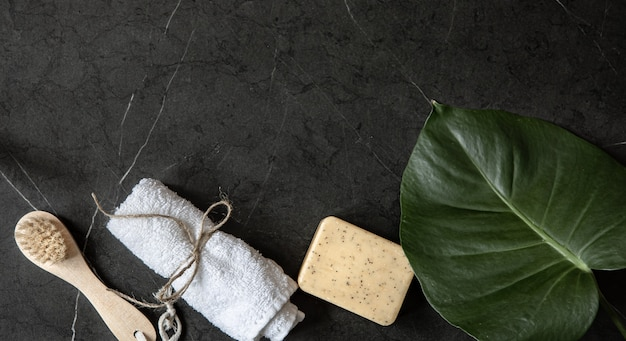 暗い大理石の表面のコピースペースにボディブラシ、タオル、石鹸のある静物。ボディケアのコンセプト。