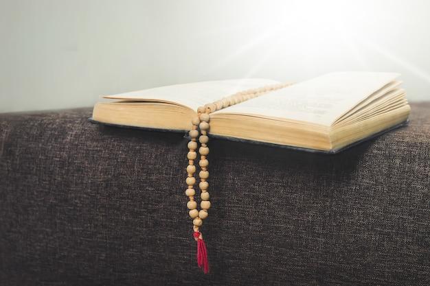 교회에서 책과 묵주가 있는 정물. 어두운 방에서 빛의 광선에 구슬이 있는 거룩한 책. 묵주와 함께 거룩한 책의 봉헌. 종교와 기도의 개념