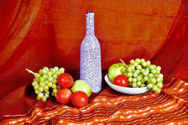 Натюрморт с бутылкой и фруктами Premium Фотографии
