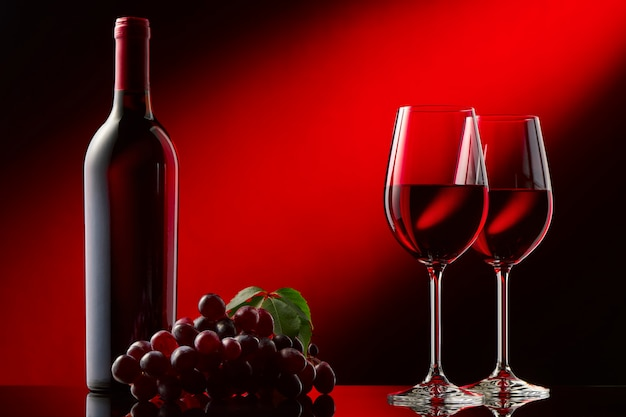 Still life with a bottle of red wine, glasses and grapes. black and red background.