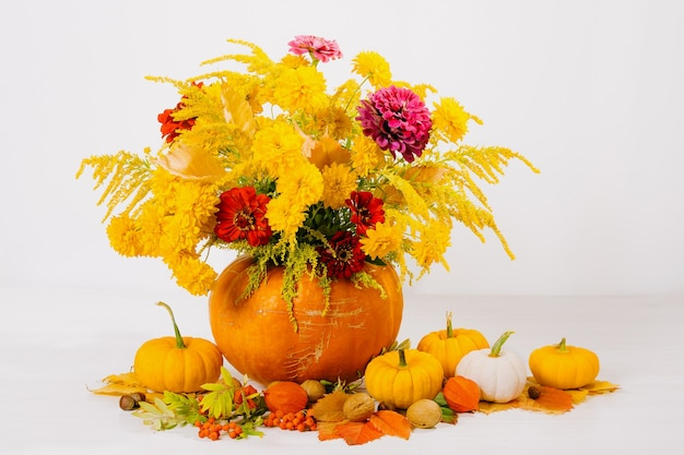 Still life with bouquet of flowers in orange pumpkin on table decoration for thanksgiving day