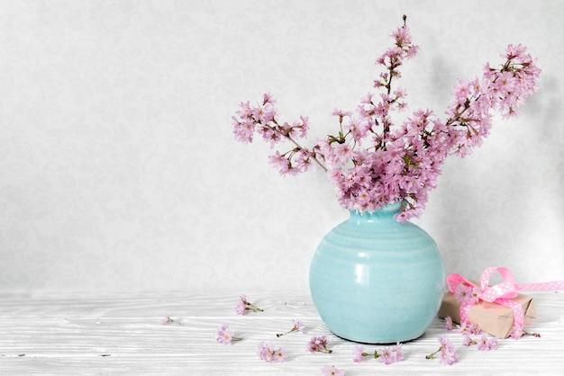 Натюрморт с букетом цветущих вишневых веток или сакуры в вазе с подарочной коробкой на белом столе
