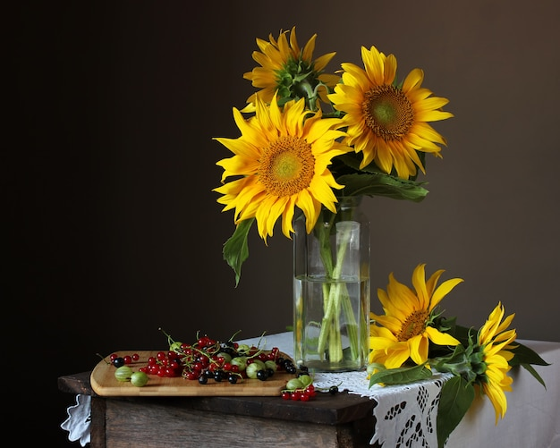 Still life with a bouquet of sunflowers and garden berries