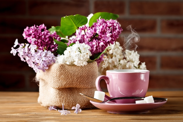 Still life with branches of lilac and a cup of coffee on a wooden table.