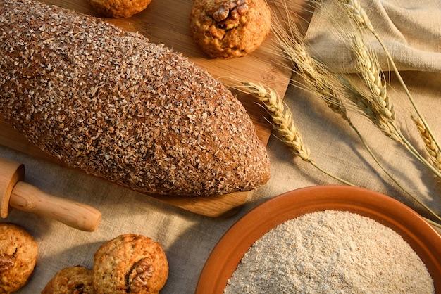 Натюрморт с хлебом, кексами, печеньем, тарелкой спельта-муки на фоне ткани из конопли. вид сверху.
