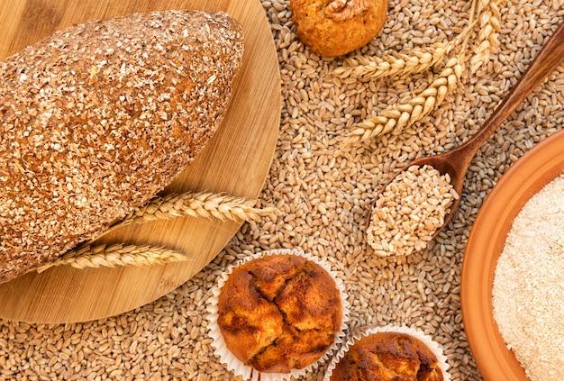 Натюрморт с хлебом, маффинами, печеньем, колосками, тарелкой муки из полбы и ложкой с зернами. он находится на фоне разбросанных крупинок спельты. вид сверху.