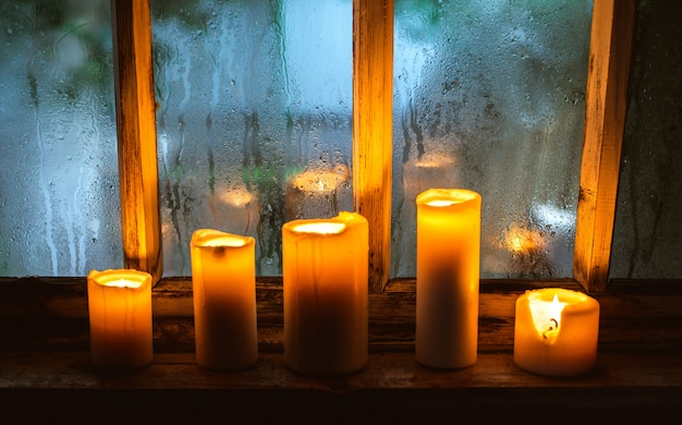 Still life with burning candles in an old country house near a wooden wet window in the autumn evening.