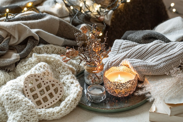 Still life with candles in candlesticks, decor details and knitted items. the concept of valentine's day and home decor.