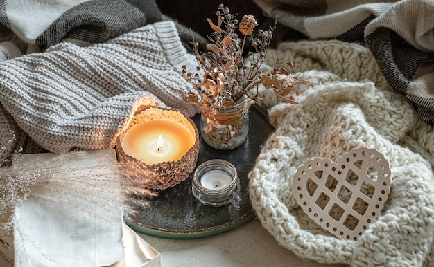 Natura morta con candele in candelieri, dettagli decorativi e oggetti lavorati a maglia.