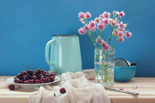 Still life with cherries and a bouquet of aquilegia on the table.  ripe berries in a plate.