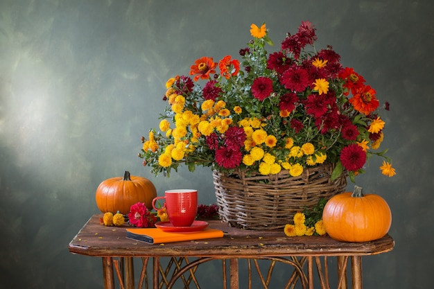 Still life with chrysanthemums in basket and pumpkins on wood shelf
