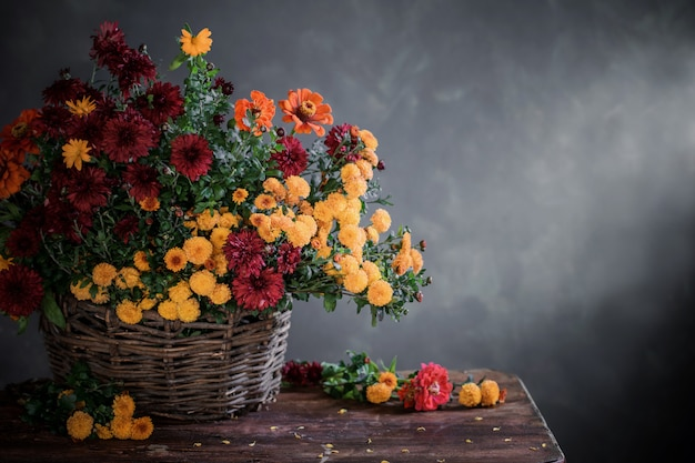 Still life with chrysanthemums in basket  on wood shelf