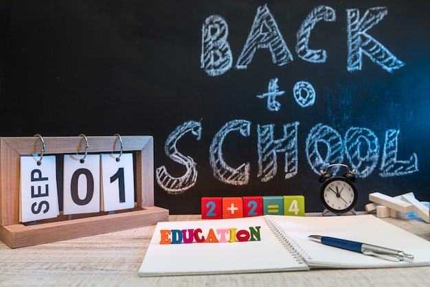 Натюрморт с часами, письменными принадлежностями, книгой и яблоком на доске с текстом обратно в школу.