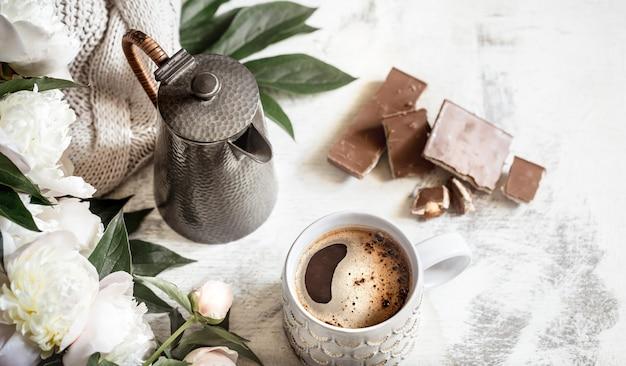 Natura morta con una tazza di caffè e fiori