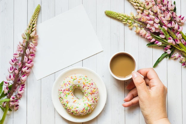 Still life with a cup of coffee and lupine flowers donut notepad on a light wooden table. copy space