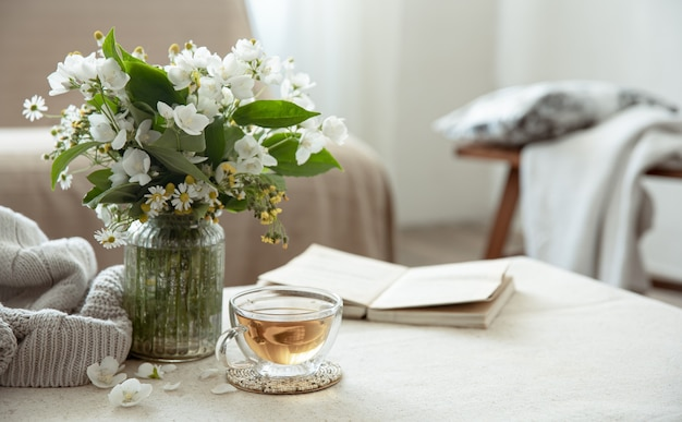 Still life with a cup of herbal tea, a bouquet of flowers, a book and a knitted element on a blurred background.