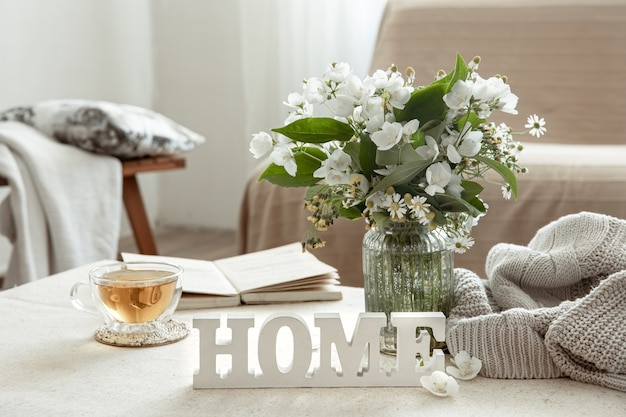 Still life with a cup of herbal tea, a bouquet of flowers, a book and a wooden decorative word home.
