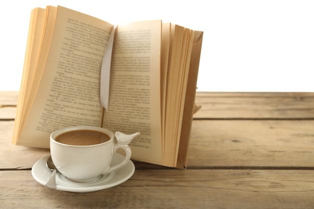 一杯のコーヒーと木製のテーブルの上の本のある静物、