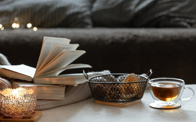 Still life with a cup of tea, books and a burning candle in a beautiful candlestick. home comfort concept.