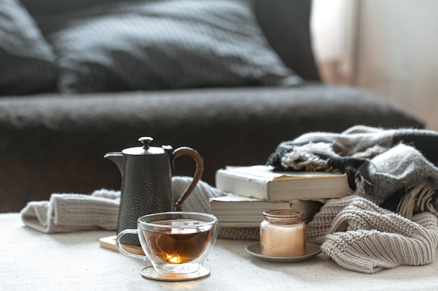 Still life with a cup of tea, a teapot, books and a candle in a candlestick. home comfort concept.