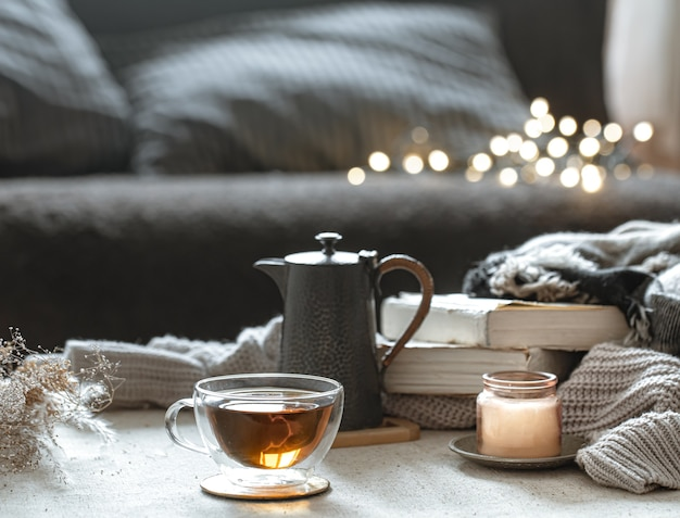 Natura morta con una tazza di tè, una teiera, libri e una candela in un candeliere con bokeh.