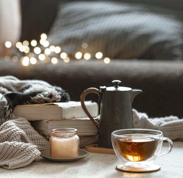 Natura morta con una tazza di tè, una teiera, libri e una candela in un candeliere