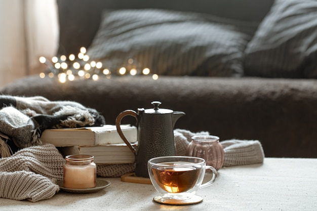 Still life with a cup of tea, a teapot, books and a candle in a candlestick