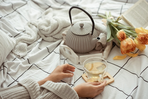 Still life with a cup of tea, a teapot, a bouquet of tulips in bed close up. weekend and spring morning concept.
