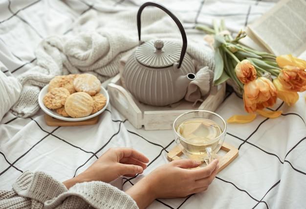 Natura morta con una tazza di tè, una teiera, un mazzo di tulipani e biscotti a letto. concetto di fine settimana e mattina di primavera.