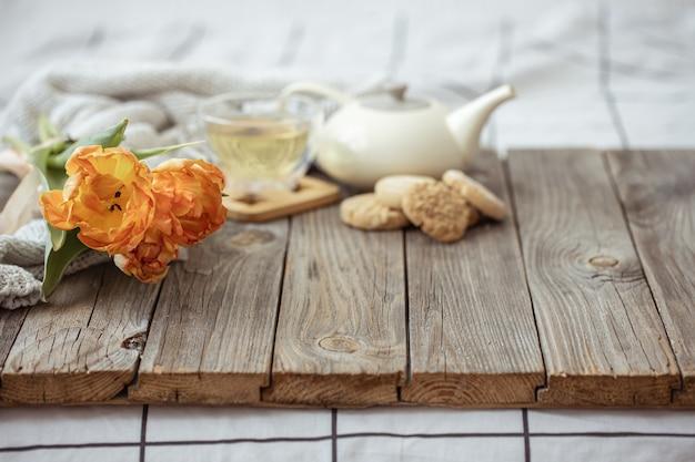 Natura morta con una tazza di tè, una teiera, biscotti e un mazzo di tulipani