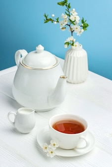 Still life with a cup of tea, a teapot and a vase on a blue background.