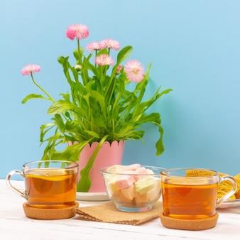 Натюрморт с чашками чая, кусочками торта, букетом розовых цветов в розовом горшке, зефиром