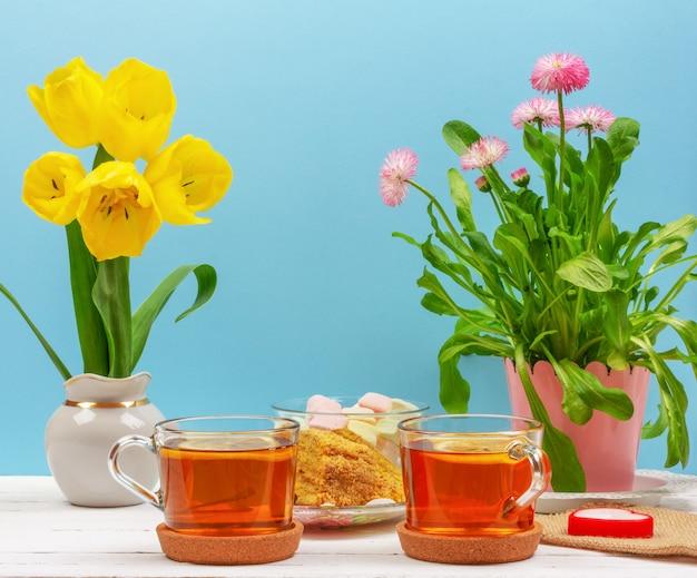 Натюрморт с чашками чая, кусочками торта, букетом розовых цветов, зефира и желтых тюльпанов