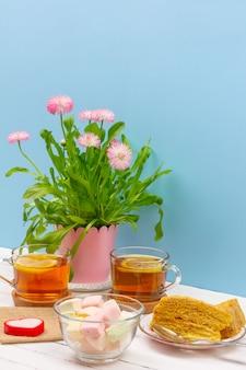 Натюрморт с чашками чая, кусочками торта, букетом розовых цветов, зефиром