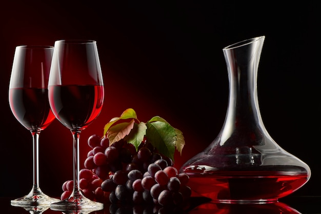 Still life with a decanter of red wine, glasses and grapes.