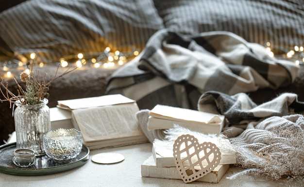 Still life with a decorative heart, books and cozy things on a blurred background with bokeh. the concept of valentine's day.