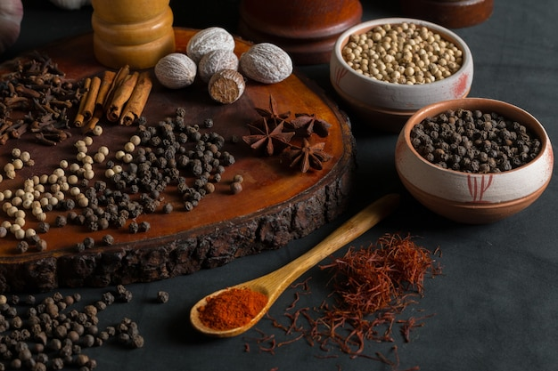 Still life with different kind of spices like pepper, nutmeg, cinnamon, and paprika on a black background.