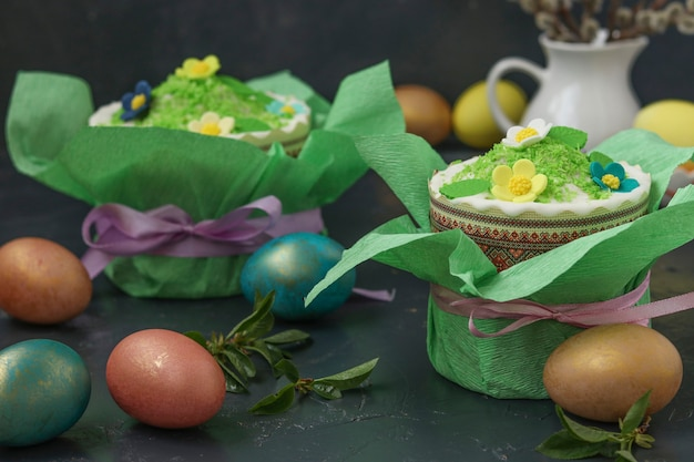 Still life with easter cakes in gift paper and multi-colored easter eggs on a dark background, horizontal orientation, closeup