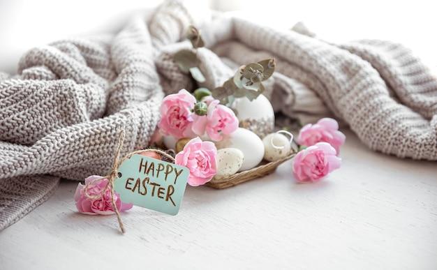 Natura morta con uova di pasqua, fiori freschi e la scritta happy easter sulla cartolina