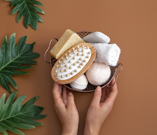 Натюрморт с женскими руками, массажной щеткой, бомбочками для ванн, мылом и полотенцем в корзине с листьями, вид сверху.
