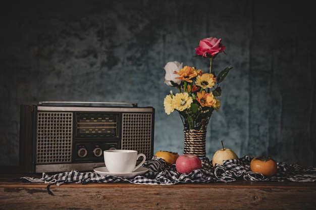 Still life with flower vases with fruits and retro radio