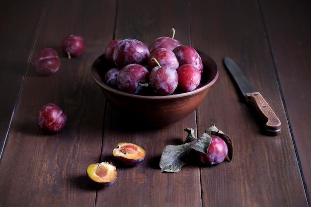 粘土のセラミックボウルに新鮮な熟したプラムと暗い木の表面にナイフがある静物。素朴なスタイル。収穫、秋、健康的でベジタリアン料理のコンセプト。セレクティブフォーカス。