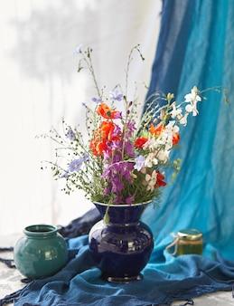 青い花瓶に新鮮な野生の花のある静物