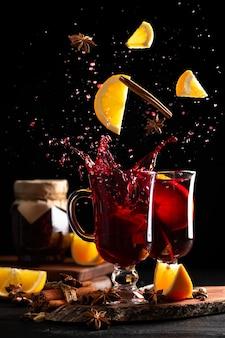 Натюрморт с полными бокалами глинтвейна и падающими специями и фруктами, брызги вина разлетаются в разные стороны