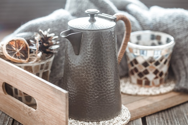 Натюрморт с предметами домашнего декора, чайниками и стаканом чая на деревянном столе в интерьере гостиной, домашняя концепция