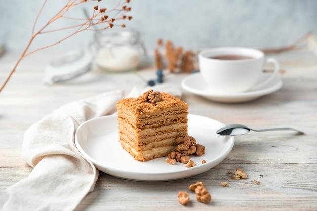 Натюрморт с медовым пирогом и грецкими орехами на мягком светлом фоне. вид сбоку, горизонтальная ориентация