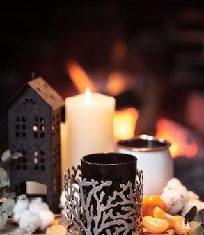 ホットドリンク、キャンドル、燃える火に対する装飾のある静物。暖炉のそばで夜のリラクゼーションのコンセプト。